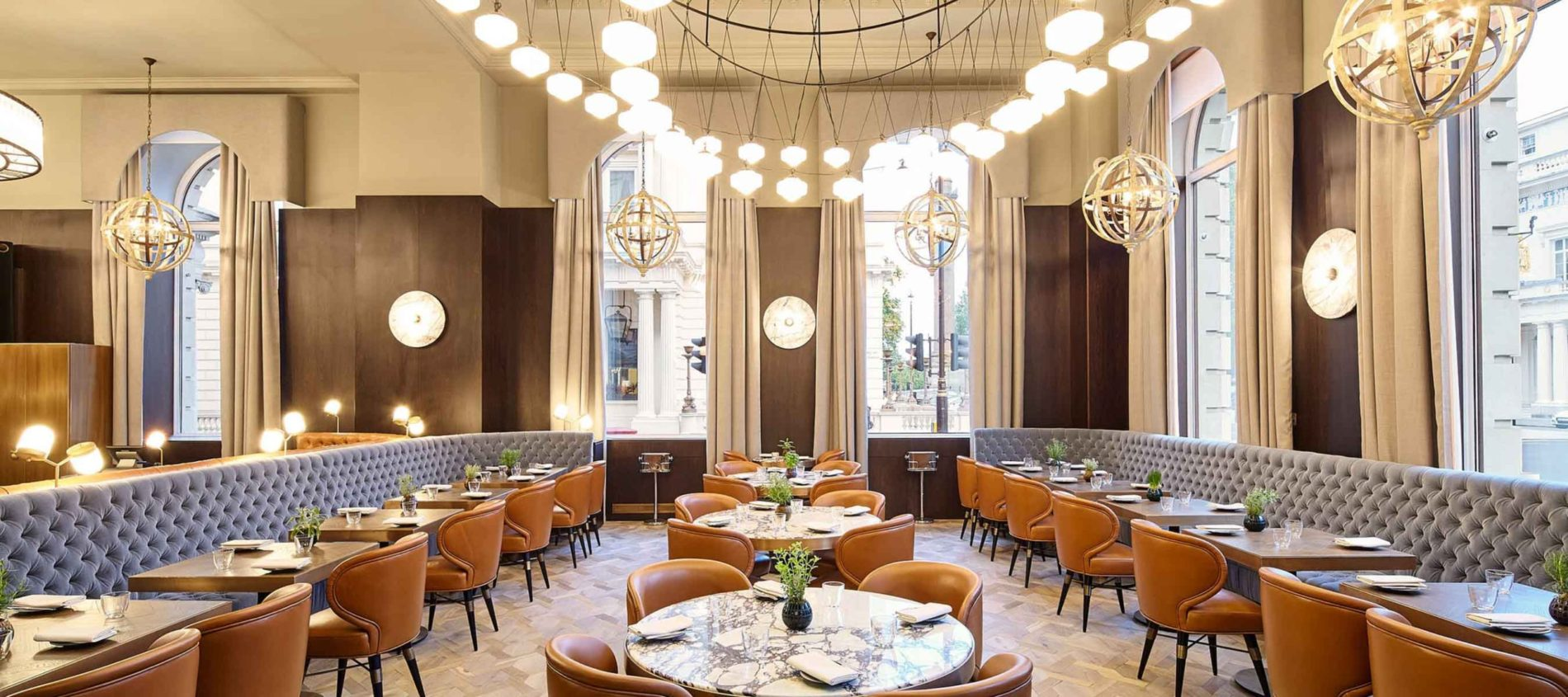 Large room high ceilings two pale blue banquettes opposite toffee leather chairs in restaurant