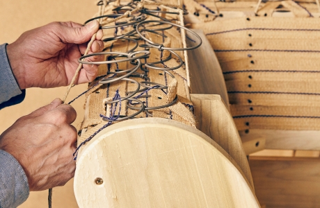 Man pulling strings through wires, upholstery