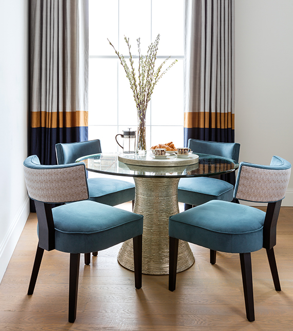 Four blue upholstered Kitchen chairs around glass table