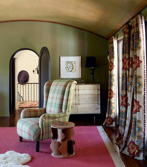 Tartan wing chair in bedroom with pink carpet and green walls