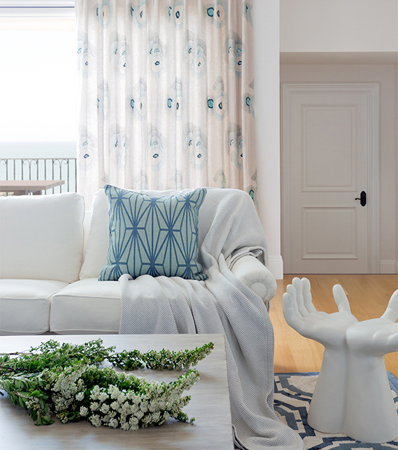 White room with white sofa, blue scatter cushion and palm seat