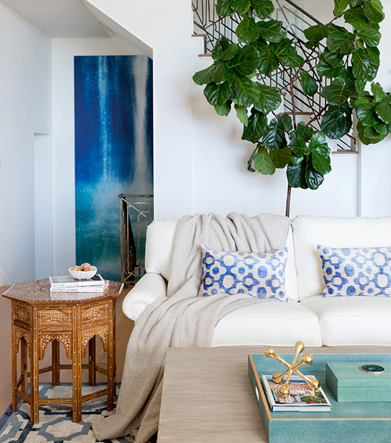 White room with white sofa, blue scatter cushions and greenery above