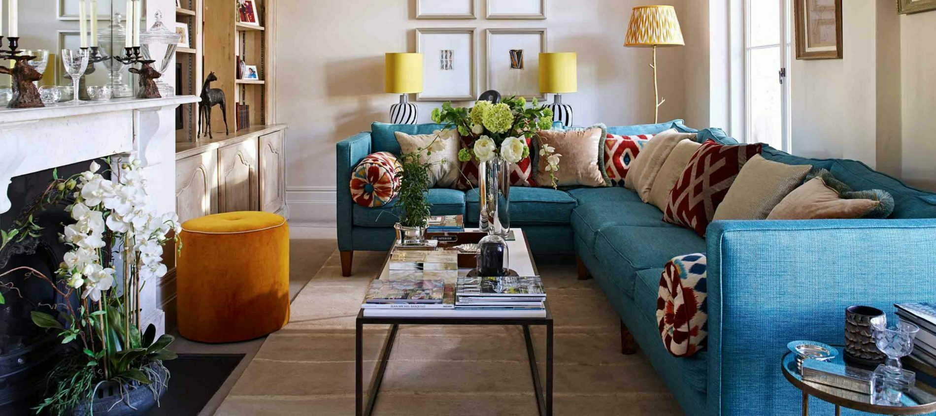 Blue L Shaped Sofa with red and white patterned scatter cushions and coffee table