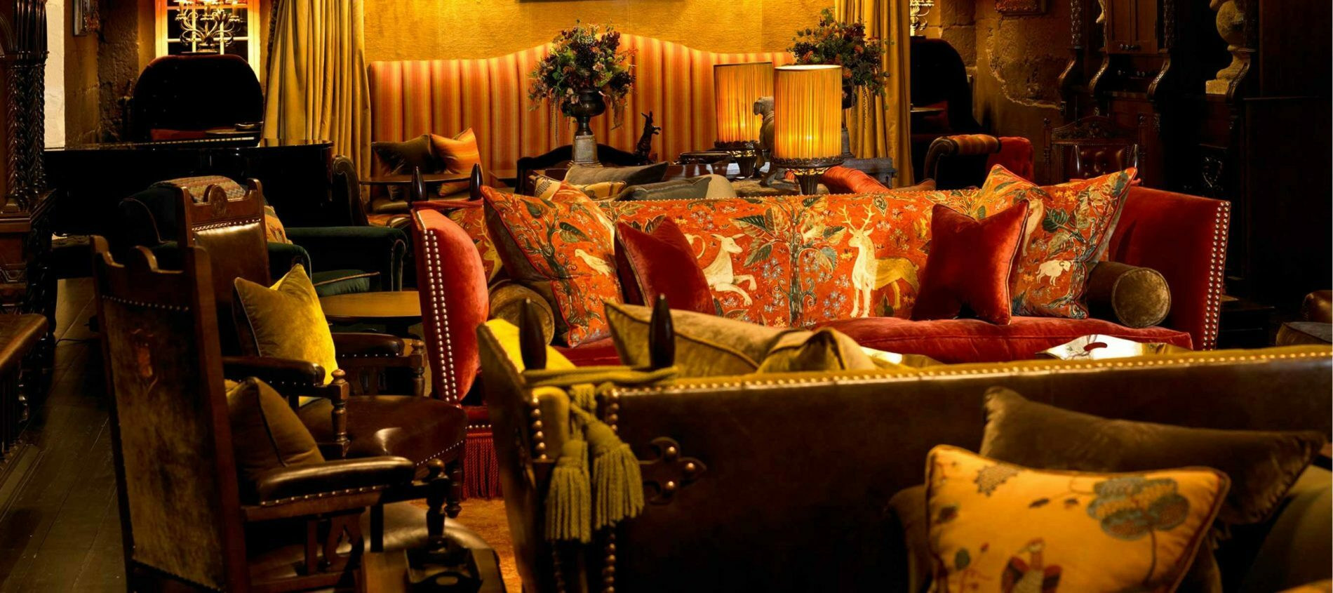 Firelit room with red sofa and other soft furnishings
