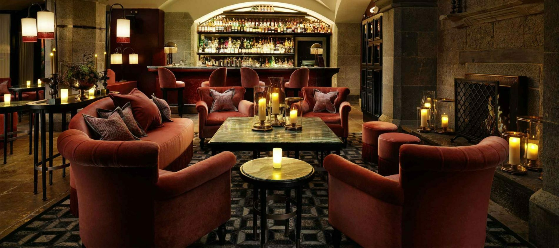 Wide angled candlelit bar with red soft furniture