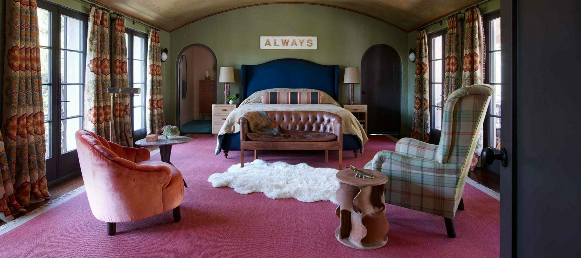 Large bedroom with pink carpets and green walls, with small sheepskin rug