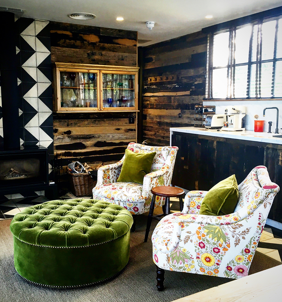 Patterned Arm Chairs with green scatter cushions and green buttoned pouffe