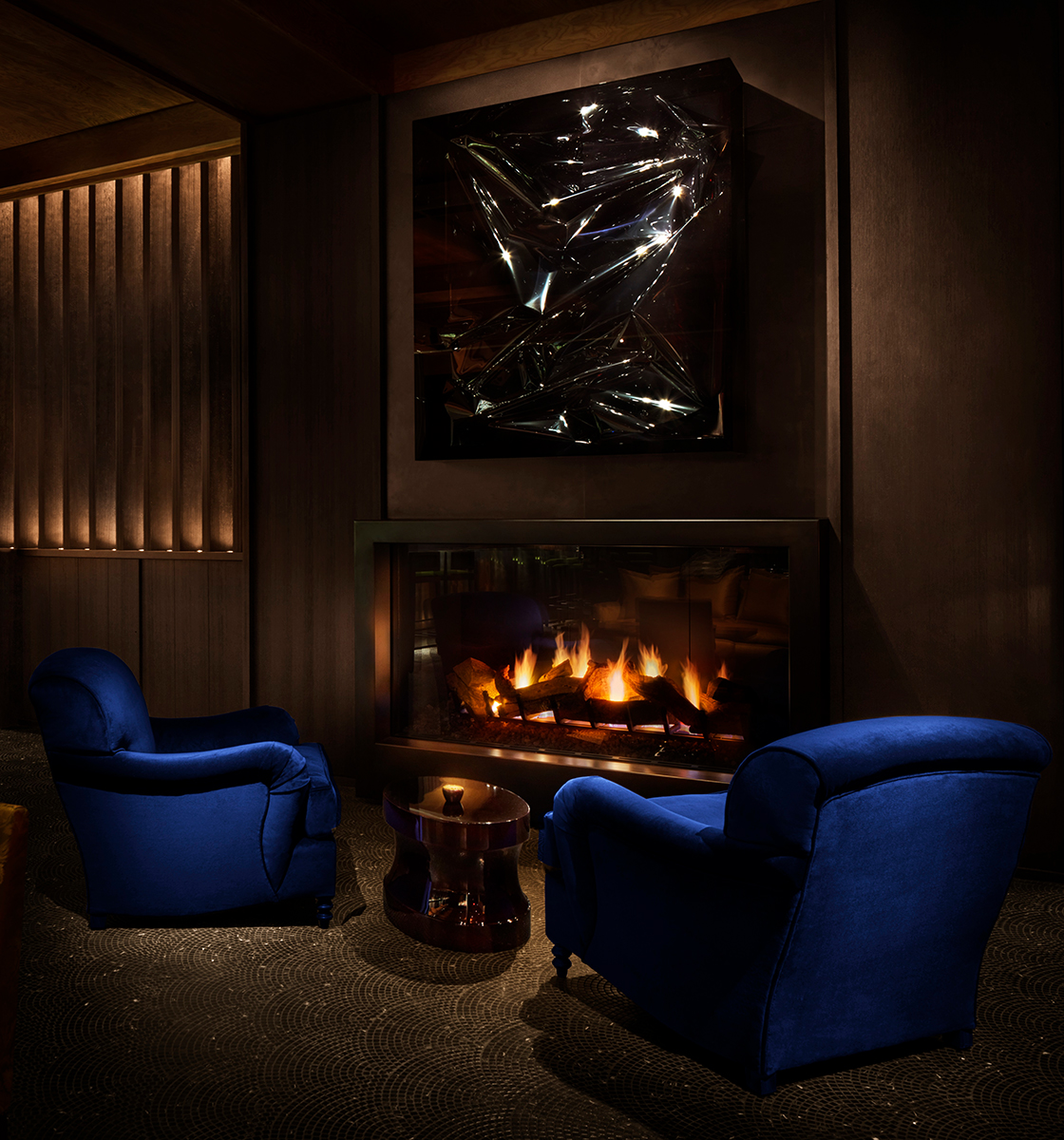 electric Blue Arm Chairs around fireplace with sliver sculpture above