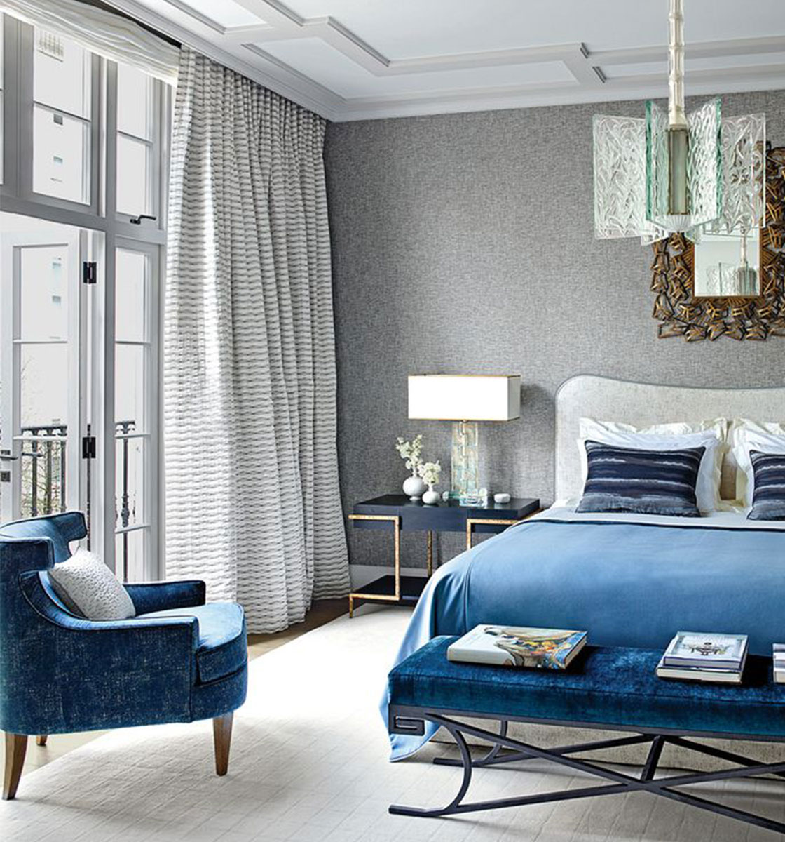 blue chair in bedroom with blue throw on bed