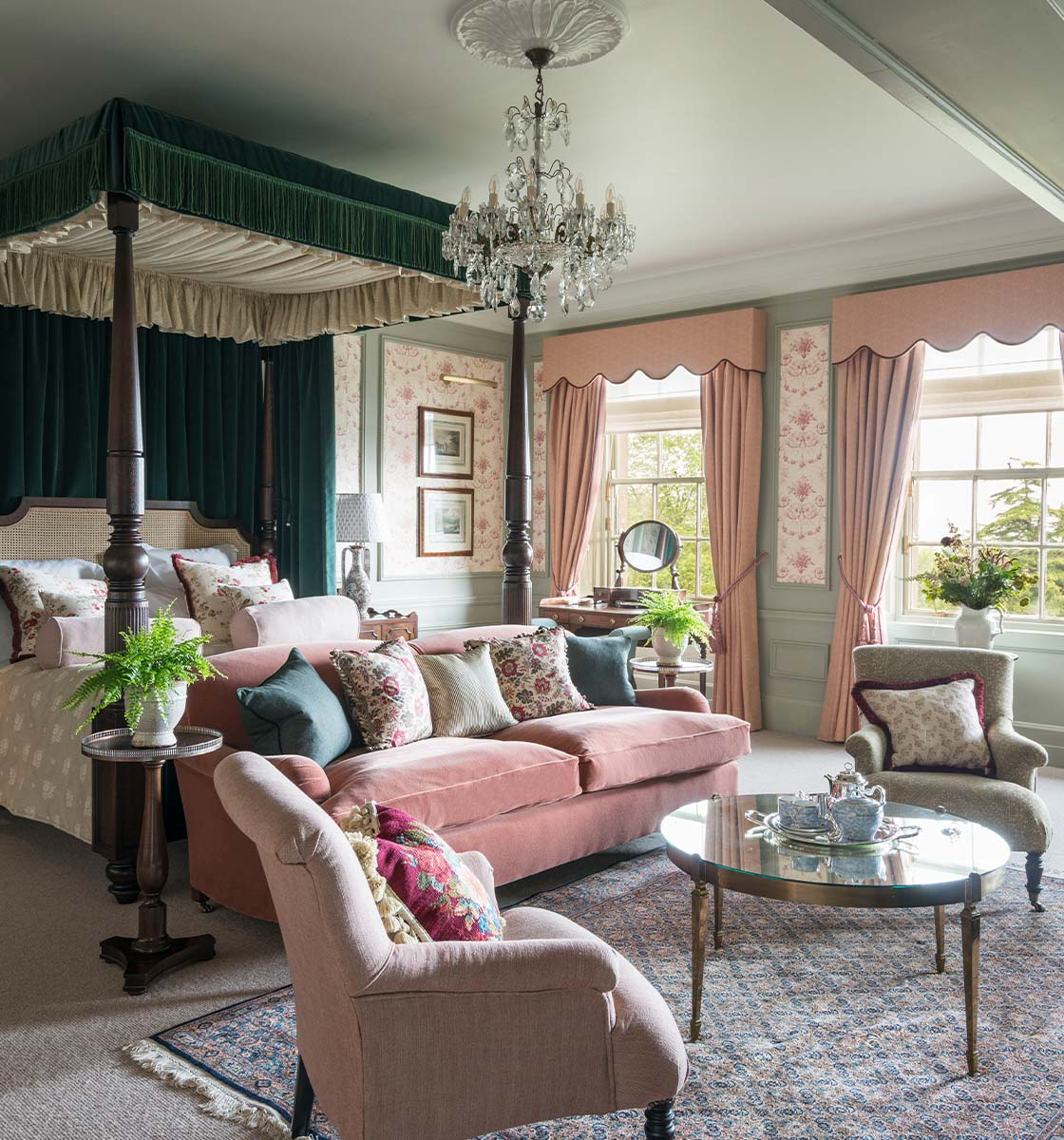 Bedroom with four poster bed and pale pink sofa