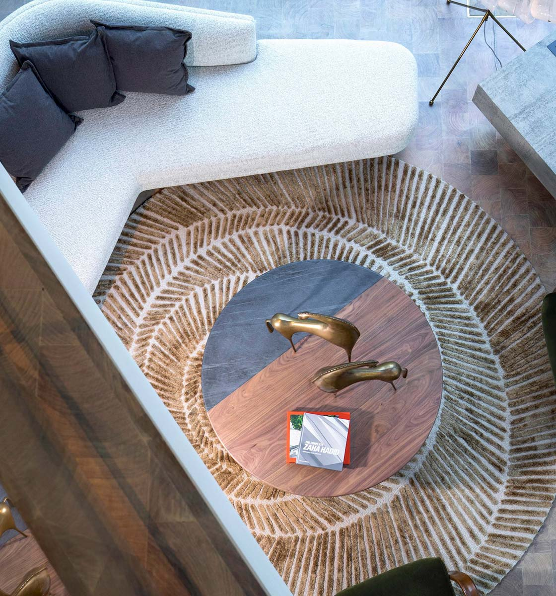 View from ceiling of spiral rug, coffee table and edge of sofa
